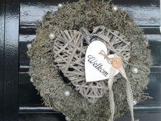 Krans omwikkelt met rendier-mos versiert met rieten hart en parels