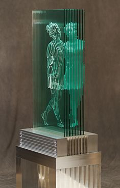 "At the intersection of art, science, and technology, Jed Malitz creates life-size glass sculptures of human figures within architectural forms. The New Orleans-based artist describes his works as ""4D sculptures of cut glass and refracted light,"" illustrating how each subject is defined both physically and non-physically through glass silhouettes and their refracted light. The silhouettes, which are based on live-subject 3D photography, suggest the physical outlines of people through holes…"