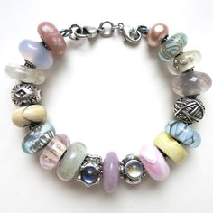 """CLOCKWISE FROM CLASP:  """"BASIC DOUBLE LOBSTER CLASP"""", """"ROSA PEARL"""", """"SMALL & BEAUTIFUL UNIQUE GLASS"""", """"SMALL & BEAUTIFUL UNIQUE GLASS"""", """"ROSE QUARTZ"""", """"BALL OF YARN"""", """"LIGHT BLUE SHADOW"""" (RETIRED), """"UNIQUE AMBER"""", """"CUSTOM MADE UNIQUE"""", """"TRINITY"""", """"LAVENDER JADE"""" (LIMITED EDITION CHINESE SERIES), """"KING & QUEEN"""" (RETIRED), """"BLUE DESERT"""", """"UNIQUE GLASS"""", """"SILVER MOUNTAIN"""", """"GREY ARMADILLO"""" (RETIRED), """"ZANZIBAR', (RETIRED), """"MOUNTAIN CRYSTAL"""" (WORLD TOUR SWITZERLAND), """"CHALCEDONY"""" (RETIRED)…"""