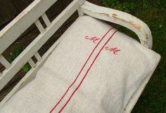 How to make a bench cushion in 5 minutes: Take a vintage Hungarian Linen Grain sack, fill with pillow, sew up sack opening.