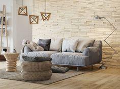 parement mural salon en pierre, plancher en bois clair et canapé droit gris