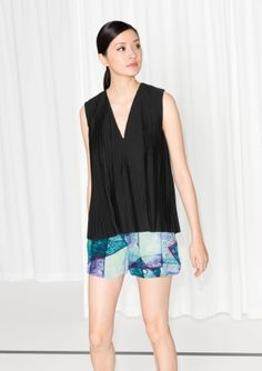 An elegantly pleated top with a deep v-neck and an all-over wide breezy fit.