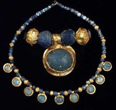 ROMAN GOLD AND GLASS NECKLACE          II-III century A.D.  Composed of nine gold pendants with double-ribbed suspension loop decorated with twisted wire, blue glass cabochons set in collar with pinched edge; fourteen  hollow, ribbed gold beads, soldered from two halves and terminated by strip-twisted wire collars; sixty-six  spherical and globular blue glass beads.