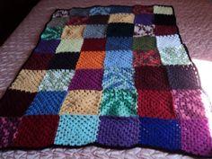 Manta de lã feita com squares de croche multicolorida.