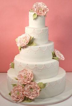 Created for a wedding with an English Garden theme, this five-tier cake was the centerpiece at an outdoor reception held at a countryside estate. The garden roses were fashioned from sugar, and the pink royal icing pattern on each tier resembled the design used on the couple's wedding stationery. Cake design by Confetti Cakes.