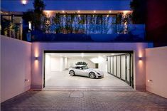 Open modern garage door & I like the huge windows with trees/shrubs in front