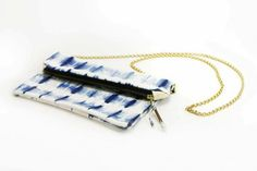 """This mult-purpose purse is created with a washed lambskin and natural indigo dye with brass detail and removable gold chain strap. Each indigo clutch is hand-created and dyed- each one is uniquely different and one-of-a-kind. Carry it as a clutch or wear it crossbody. Makes a great iPad case as well! Unlined / 12""""x10"""" unfolded/ 22"""" black strap ----- About the shop: HACIENDA Austin showcases locally sourced and globally inspired custom furnishings and curated gifts for the modern ranch…"""