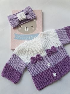 Cardigan and bow for baby worked in garter stitch, using shades of purple.