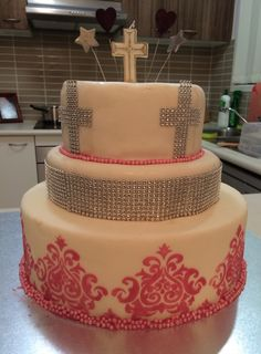 3 tier cake I made for my daughters Baptism Baptism/christening cake Top tier mud cake Middle tier red velvet cake Bottom tier dummy cake  Covered in white mud fondant Diamanté cross and skirt  Royal icing for the stencilling on bottom tier  Topped with a cross candle