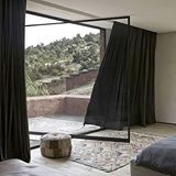 INSPIRATION: Pivot doors and dramatic curtains perfectly frame the views from this @studio_ko villa in Morocco. Pairing Parisian elements of blackened steel and aged timber with local stone and rendered cement, not one detail in this space is out of place. Link in profile | photo by #danglasser #estliving #travel #morocco #studioko #moroccandesign #interiordesign #oikastone #bedroomdesign