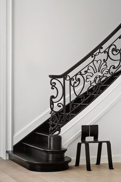 Under the staircase, Perriand's Ombre chair of black bent plywood creates an stark connection with the black iron baluster. Black Staircase, Staircase Railings, Staircase Design, Stairways, Banisters, Stair Treads, Iron Balusters, Marie Claire, Wrought Iron