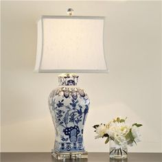 A transitional option in blue and white porcelain, this square vase table lamp presents beautiful blue and white floral designs atop a crystal base. Oblong square off-white satin shade Total lamp max, medium base socket. Blue And White Lamp, Blue And White China, White Lamps, Large Table Lamps, Table Lamp Wood, Table Lamp Shades, Lamp Socket, Outdoor Light Fixtures, Outdoor Lighting