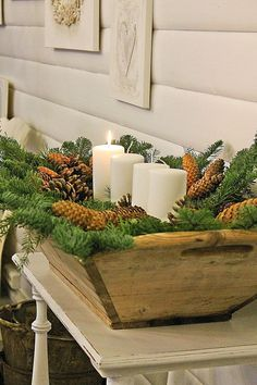 a wooden dough bowl with evergreens, pinecones and pillar candles