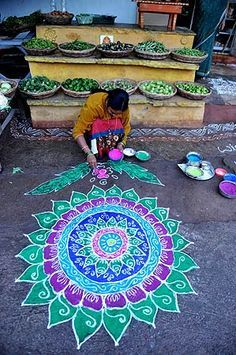 """An Indian woman applies coloured powder to her """"rangoli"""", a Hindu ritual design, in front of her house in Hyderabad on January 1, 2013. Rangolis are drawn in front of homes early in the morning with a beautiful motif to welcome relatives and friends to mark the New Year. — AFP Photo Mandala Art"""