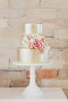 3-tier extraordinary cake with an unbelievable sateen finish in pearl with a crystal band at the bottom of each tier &  flowers in shades of white, peach, & pink delicately placed cascading down the center.