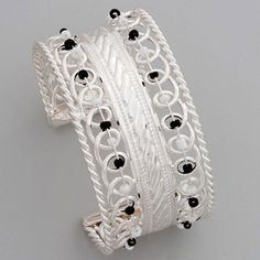 Silver-colored cuff bracelet in multiple designs featuring tiny black and white bead accents strung on silver-colored wire. The perfect piece to ground any color outfit, bright or neutral, with a touch of silver shimmer.
