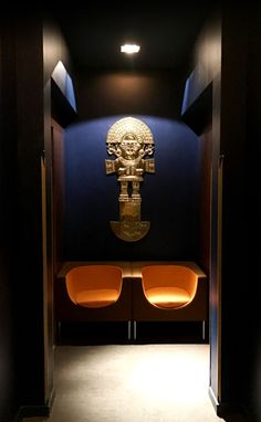 Customized aztec brass mask in INKA restaurant in 1K Hotel Paris - interior by RM Design. Waiting area in orange and blue with gold metal #tribal #waiting #mask #interior #design #dark #restaurant #hotel