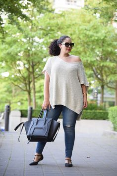Tanesha Awasthi (formerly known as Girl with Curves) wearing an off the shoulder sweater, distressed jeans, flats and Celine Phantom bag at the park in downtown Vancouver.