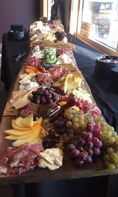Charcuterie / meat and cheese laid out on a long wood plank. Buffet style, cocktail party. For the holidays. #ttvwinepairings