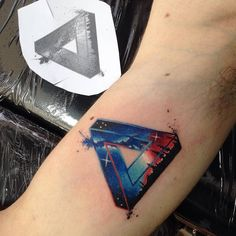 Galactic penrose triangle tattoo on the right inner arm.