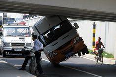 A Van is stuck under a bridge