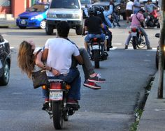 A motorcyclist carries Venezuelan model Genesis Carmona, injured during an anti-government protest in Valencia on February 18, 2014. The 21-year-old model died on February 19, 2014 after suffering a gunshot wound to the head in the protest march, a hospital source told AFP. AFP PHOTO /MAURICIO CENTENO (Photo credit should read MAURICIO CENTENO/AFP/Getty Images)