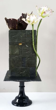 Architectural, I made my own moulds and cladded the triple barrel Cake in square/rectangular pieces to simulate Slate. In a very dark green-ish charcoal tone with gold accents...