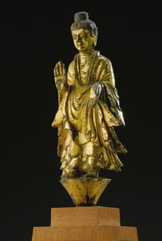 AN IMPORTANT GILT-BRONZE FIGURE OF BUDDHA NORTHERN WEI DYNASTY portrayed standing barefoot on a circular tapering base, both hands held in abhayamudra, clad in loose robes falling in crisply cast folds that flare outwards, his sharp features framed by long ears and wavy hair that covers his ushnisha, the back with rectangular cavity and two pierced tabs, wood stand and box (3) Height 7 3/4 in., 19.7 cm