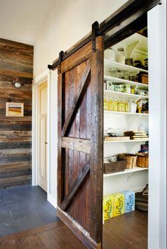 I've seen barn doors show up all over the home in the last few years. Have you noticed that? The rustic character and worn, weathered varnish looks great in a lot of different settings. Here's one example: this sliding barn door — with its heavy iron hardware — leads into a pantry! Such a cool detail.
