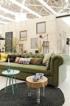 Living room with green couch and knitted carpet #stool #pillows
