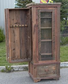 A custom barn wood cabinet with a glass door, drawer below and a hidden gun slide out in the back. LOVE this piece, when it's shut you cannot tell that the back panel slides out. Reclaimed barn wood with an oil and poly finish