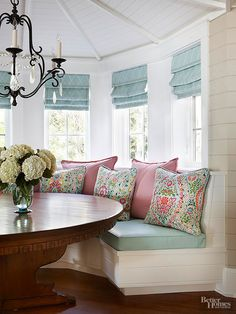A curved built-in banquette resides beneath an ocular ceiling detail in this breakfast nook. Pillows and built-ins eliminated the option for full-length draperies, so the designer chose simple Roman shades to offer privacy and to accent the architecture. The pale blue fabric offers a subtle pattern for interest without overpowering the drama of the bay.