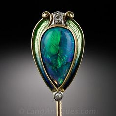 An entrancing peacock-colored, pear-shape black opal, weighing 1.50 carats, is exotically presented in a shimmering green enamel and diamond...