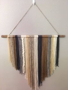 This beautiful wall hanging would look perfect in any shabby-chic home, cottage, farmhouse or nursery! It is handcrafted with different pieces of yarn, of different colors and textures. This yarn wall hanging is a great statement piece adding a new style for any room in your home! It