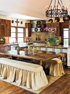 In this old-world kitchen, salvaged wood flooring inspires the entire space (and is an eco-friendly choice). Leftovers from the flooring were used to create the dining table, and pecky cypress kitchen cabinets complement the warm wood throughout.