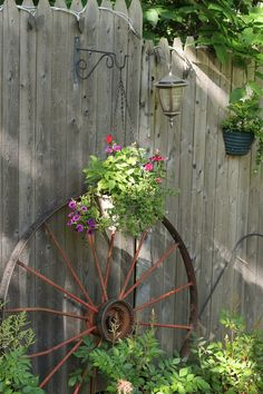 Old Wagon Wheel Up Against An Old Rustic Fence. Rusty Garden, Lawn And  Garden