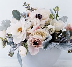 A mix of white flowers, some tinged through with pink, cut short and paired with silvery lamb's ears and eucalyptus pods yields a rich winter scene
