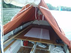 Oars in sleeves along the edges of the tent on this Minahouet (Vivier designed sail/oar boat just over 15' in length) keep the edges of the tent outboard in light winds while loop tabs bungied inboard provide more security in stronger winds. 4 floorboards temporarily fill in between the benches to provide a 6' sleeping platform.