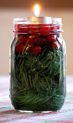 Layered pine boughs (or other holiday greenery), cranberries and water topped with a tea light, all tucked inside a mason jar is all you need for a fun, small festive centerpiece. Remember, when using candles as a centerpiece, don't use a scented candle.