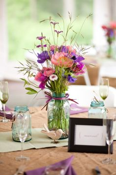 wildflowers in canning jars. Here they used ranunculus, anemones, and pink cornflowers along with grasses and flowers they gathered.