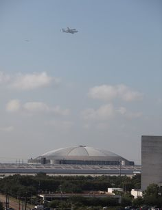 Space Shuttle Endeavor headed for retirement in Los Angeles, passing over the Houston Astrodome.