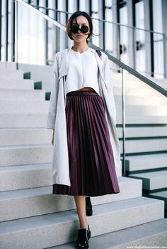 This blogger wears round sunglasses, grey trench coat, white shell top, pleated burgundy skirt and oxfords.