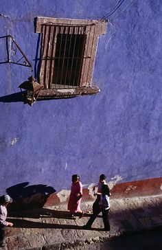 Going home: people walking along the colourful streets of San Miguel de Allende past a building with bars on the window