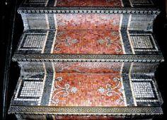 Escada revestida de mosaico.. Mosaico no espelho e no piso. Na borda do piso, decoração com faixas inspiradas na arte grega. Ornato em forma de friso . Gregas de 4 tempos se repetem em todos os degraus na escada - Acesso 1º para o 2º andar do MNBA.
