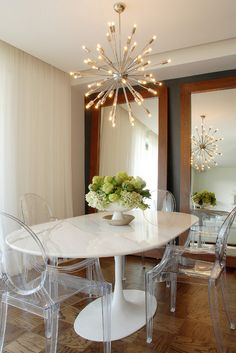 In lieu of artwork, a pair of handsomely framed walnut mirrors directs the attention back to this stunning Sputnik chandelier.