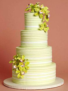 Contemporary, chartreuse green, 5- layer, round wedding cake accented with sugar or gum paste cymbidium orchids.
