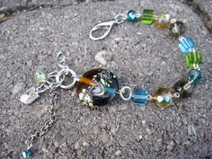 """'Pixie' Tones of purple, turquoise, green and amber crystals, with a lampworked glass bead make this bracelet unique and funky. The asymmetrical design allows for this bracelet to be worn every way possible. Included charms and dangling glass beads make this a great and fun piece! 7 1/2""""L adjustable. $27 #jewelry #women #fashion"""