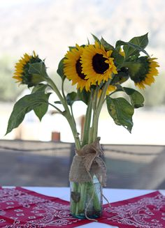 Western theme outdoor centerpiece. Burlap wrapped Mason Jar filled with Sunflowers and red bandana runner.