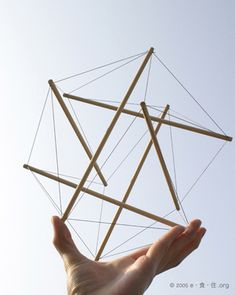 6 strut tensegrity structure held in a hand.