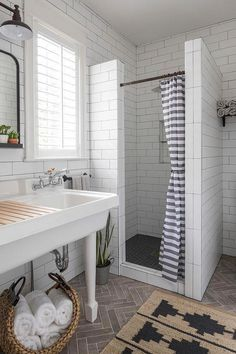 Beautifully appointed white and gray bathroom features a gray stripe shower curtain hung from an oil rubbed bronze curtain rod in front of a horizontal white tiled walk in shower contrasted with black hexagon floor tiles. Striped Shower Curtains, Bathroom Interior Design, Small Master Bathroom, Shower Stall, Man Bathroom, Bathroom Towels, Bathroom Shower, Bathroom Decor, Bathroom Towel Storage
